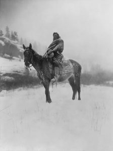 Crow Tribe Man on Horseback in the Snow.