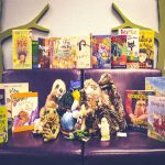 Group of puppets with books surrounding them