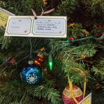 Giving Tree tag hanging on tree with ornaments