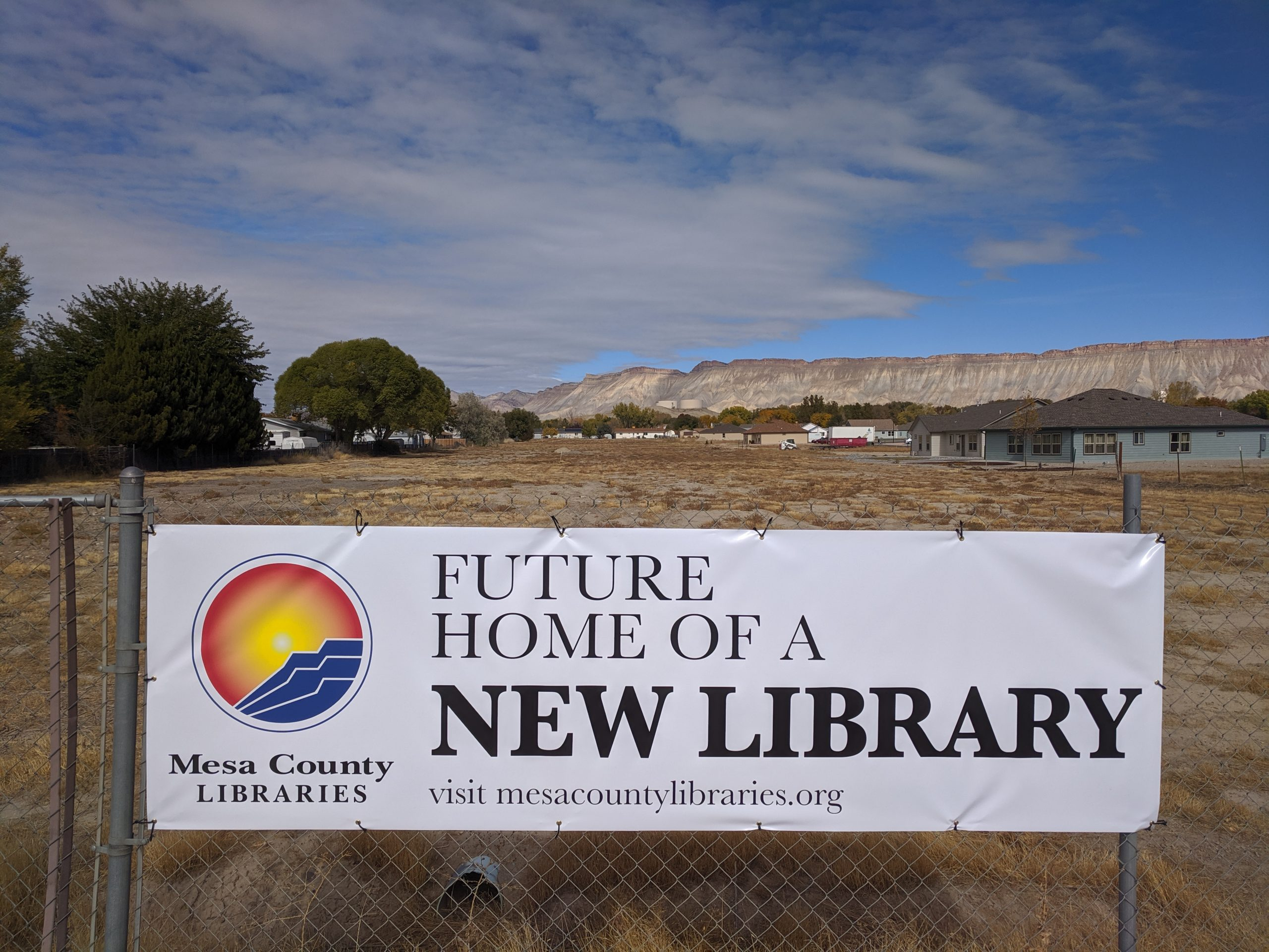 """Open field with """"Future Home of a New Library"""" sign in foreground"""