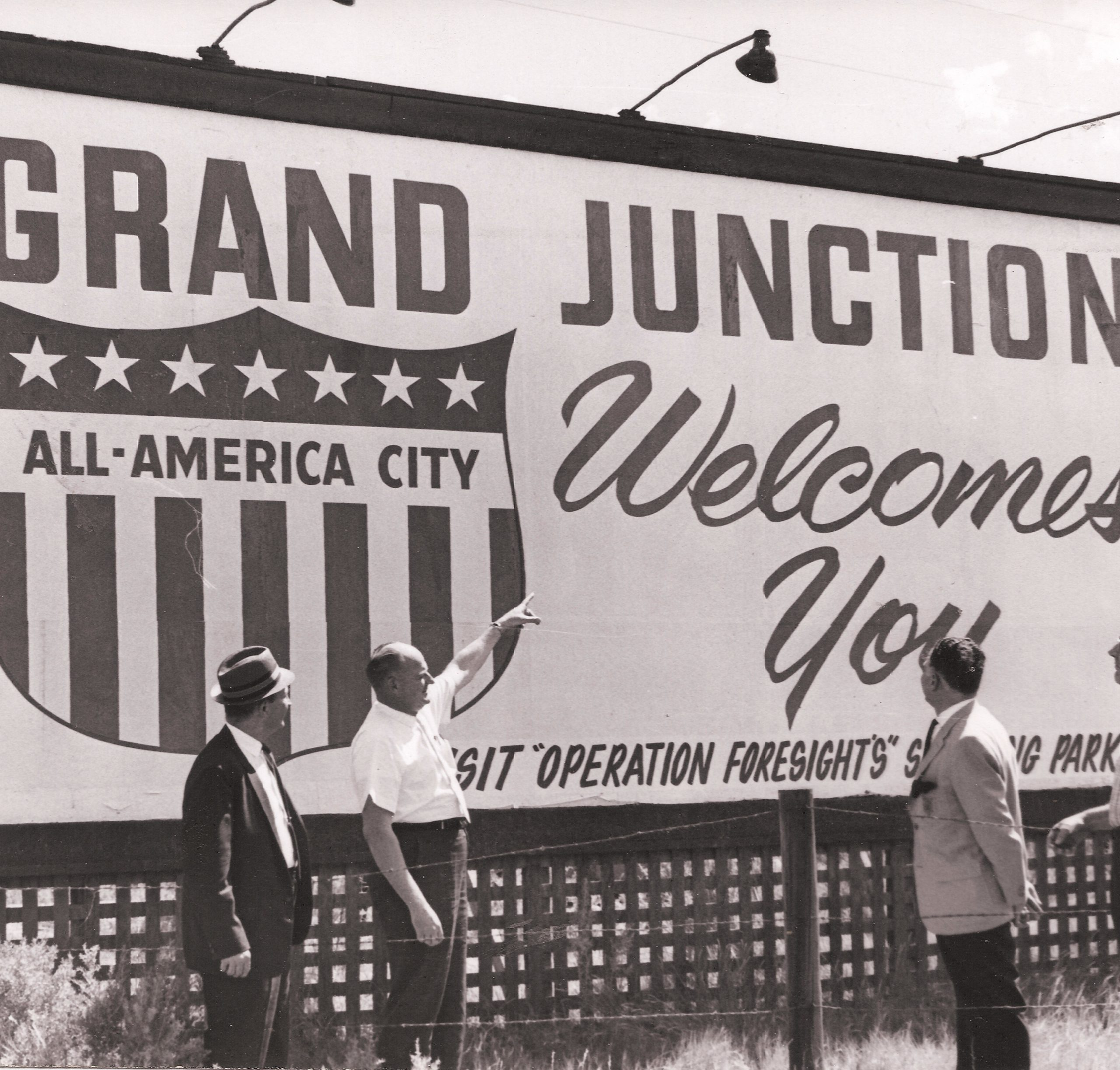 "1963 black-and-white photo of several men looking at a ""Grand Junction Welcomes You"" billboard"