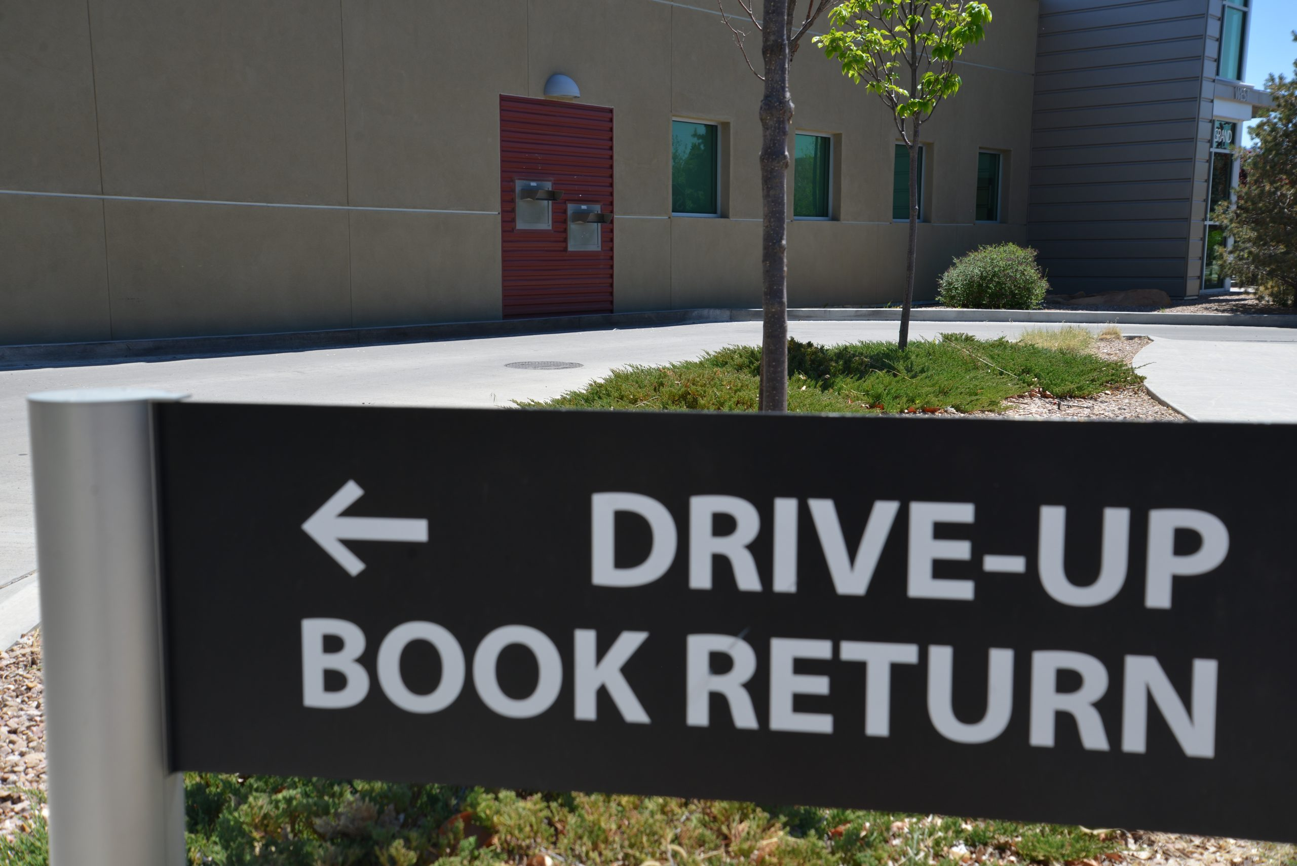 "Photo of a ""Drive-Up Book Return"" sign in front of a library book drop"