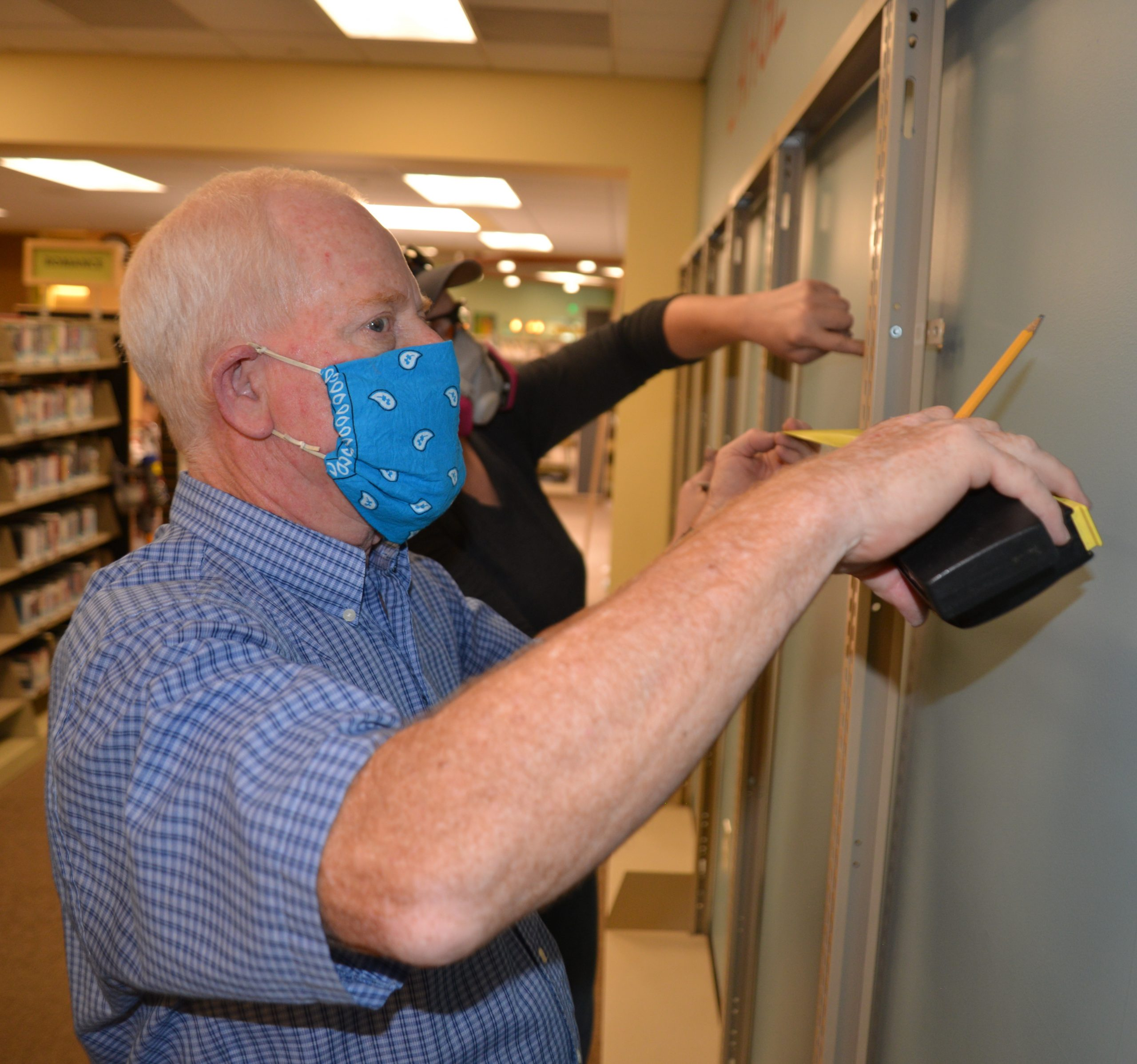 Library staff wearing masks install new shelving on a wall in a library buidling