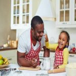 a father laughing and cooking with his daughter.
