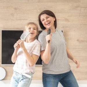 Mother singing to hairbrush with daughter.