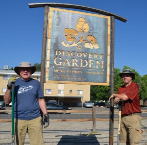 Volunteers stand next to new Discovery Garden sign