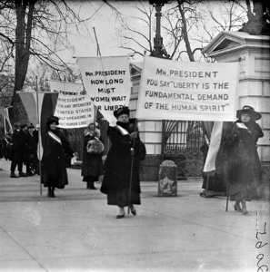 Old photo of women marching the streets with picket signs in favor of suffrage.