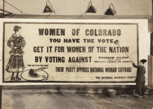 Old photo of a billboard telling women of Colorado to vote against anti-suffrage candidate, Woodrow Wilson