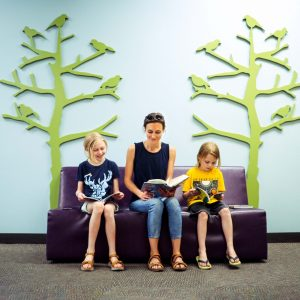 Picture of a family reading at the library.