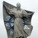 Dignity Sculpture in Chamberlain, South Dakota - a silver sculpture of a Lakota woman with her arms spreading a blanket around her body.